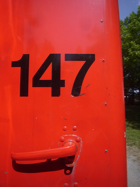 Helvetica numerals 147 on scarlet-red machinery