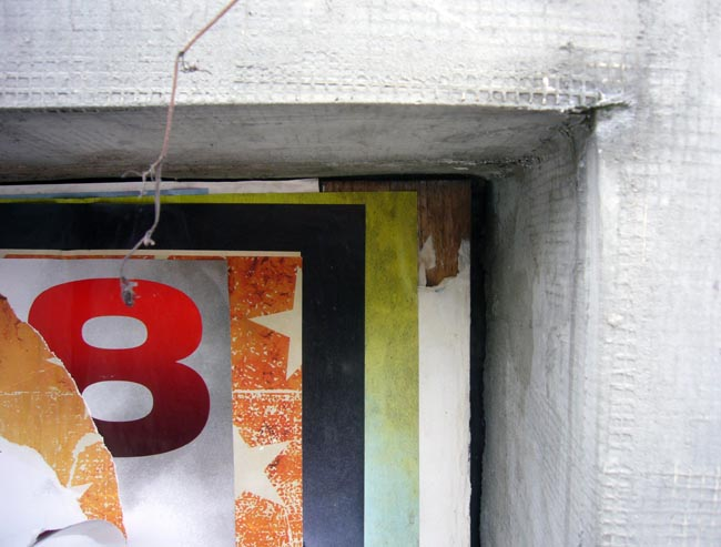 8 seen through layers of torn-off ad posters