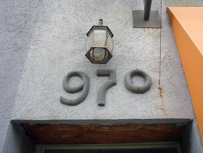 970, with descending 9 and 7, written in extruded-looking numbers raised considerably off a building's stucco wall