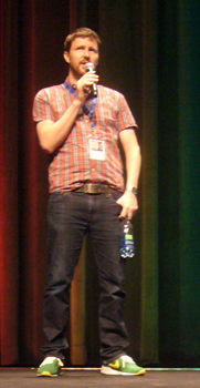Andrew Haigh onstage, in untucked shirt and green sneakers