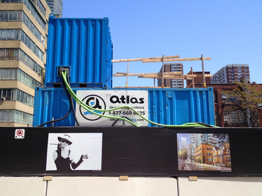 Two blue shipping containers atop construction hoarding emblazoned with photo of fashionable female model