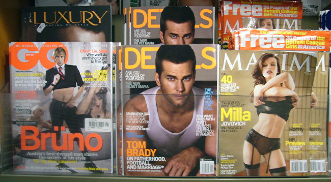 Brüno baring midriff on 'GQ' cover; Tom Brady in tank top on 'Details' cover; Milla Jovovich pulling off top on 'Maxim' cover