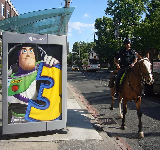 Mounted policeman clomps past bus shelter showing Buzz Lightyear