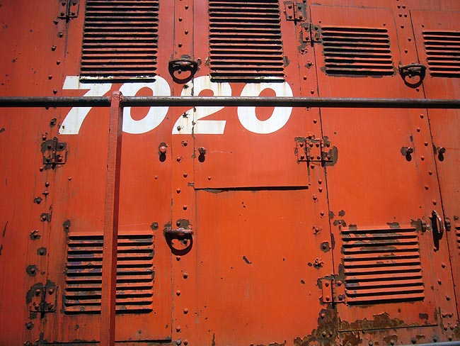7020 in Helvetica Bold Italic on a rusty railcar