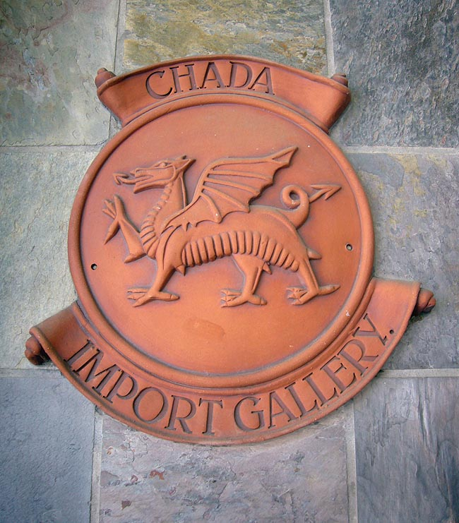 Terracotta shield on stone tile shows wingéd dragon and legend CHADA IMPORT GALLERY in Belwe