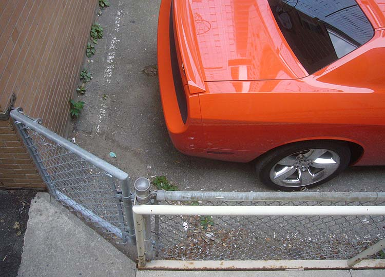 Corner of orange Dodge Charger inside angled fencing