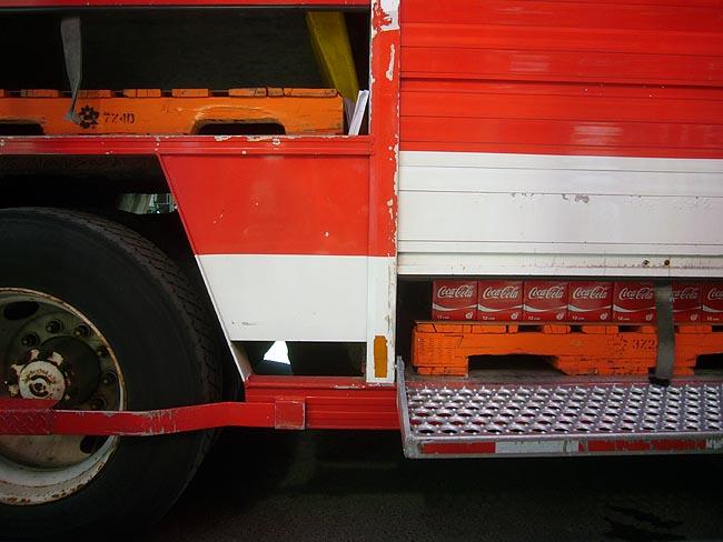 Cases of Coke hidden inside small trap door at bottom side of orange truck