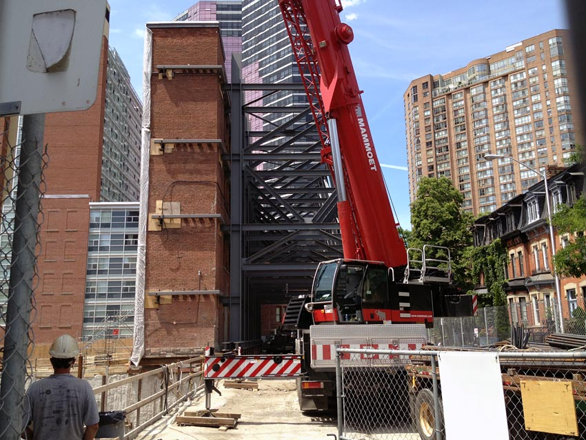 Mass of steel I-beams lean into a brick building as a red crane looms in foreground