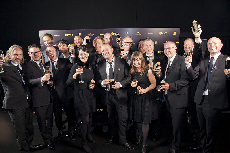 A dozen or so designers, in black tie and gowns, hold up champagne flutes and D&AD awards before a backdrop