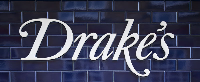 Swash italic Drake's logotype on deep-blue tile