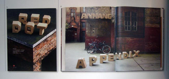 RED DOT and ANHANG APPENDIX are spelled out in wooden block letters arrayed on an old industrial building