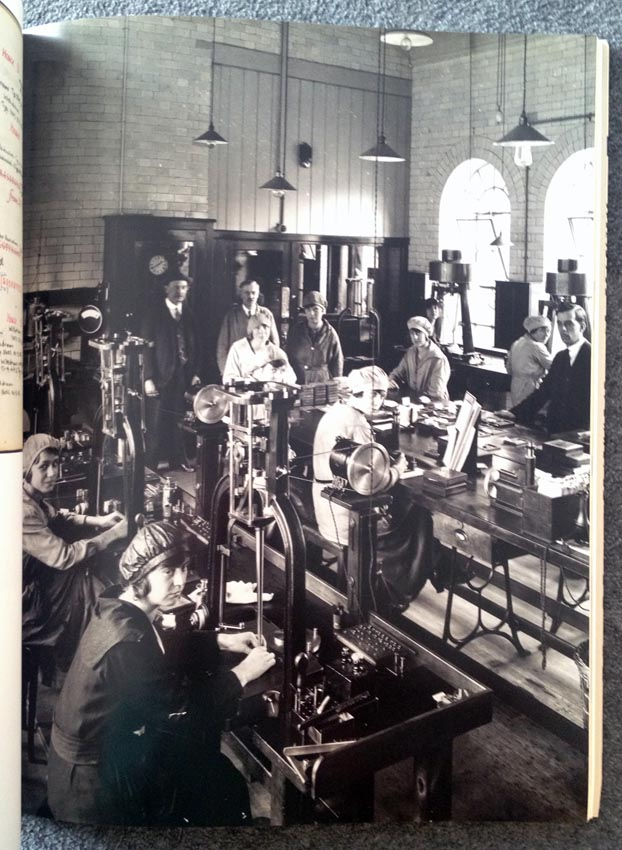 Massive composing room with ladies in hats looking at the camera