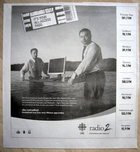 Oriental dude and white dude carry a table with a computer monitor across a lake