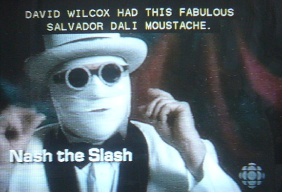 Nash the Slash, face completely bandaged, in round black shades, and wearing a white hat: David Wilcox had this fabulous Salvador Dalí moustache