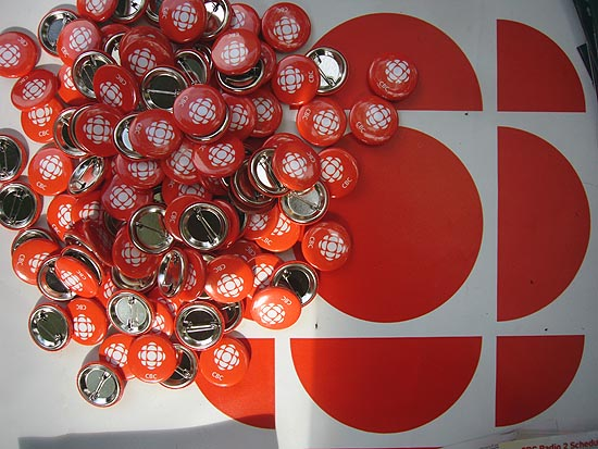 Mass of red CBC lapel buttons atop red CBC logo