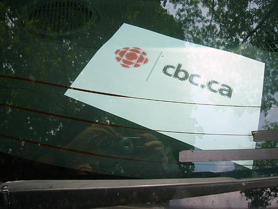 Blurry printout on dashboard under windshield shows pixelated CBC logo and cbc.ca