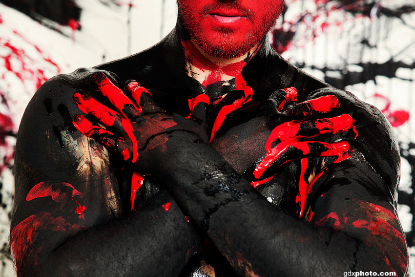 Shirtless man in black bodypaint has red-painted face, red-paint-smeared fingers crossed over chest