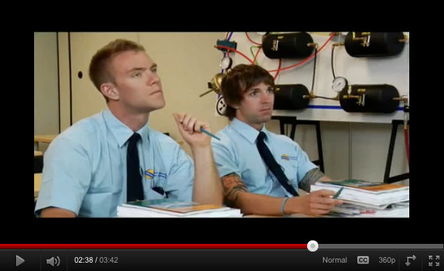 Screenshot: Easton and Horlor in blue short-sleeved BC Transpo shirts and clip-on ties in classroom