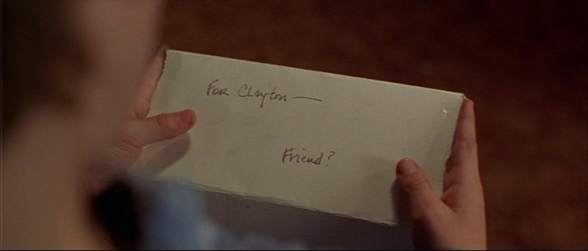 "Young boy holds a folded page reading ""For Clayton—Friend?"