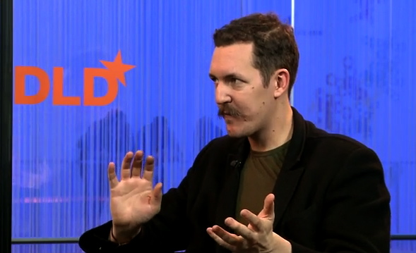 Ben Hammersley, with moustache, gestures before bright blue background with orange DLD logo