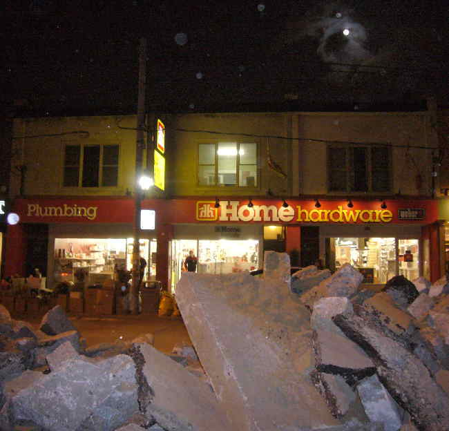 Under a cloud-obscured full moon, a Home Hardware store sits behind piles of torn-up pavement