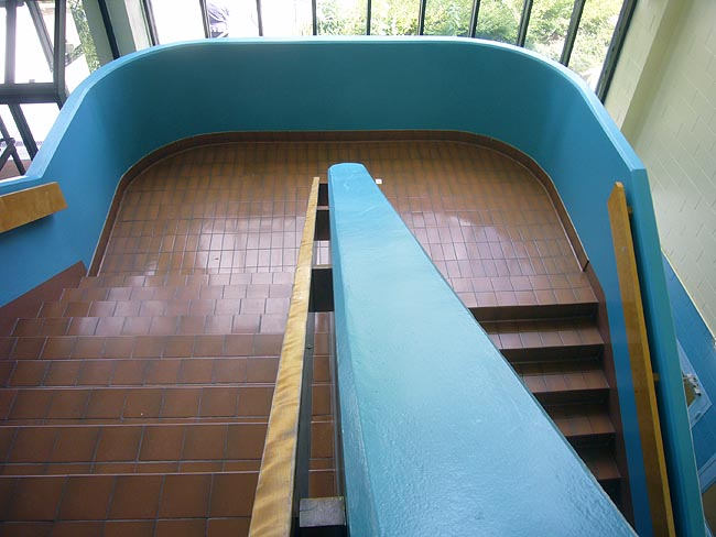 Varnished wooden stairs inside solid, curved, bright-blue walls