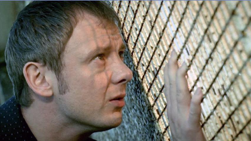 John Simm peering through window grating