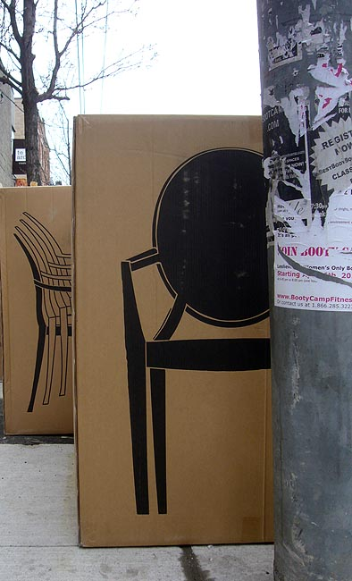 On sidewalk: Boxes with silhouette and profile of chair