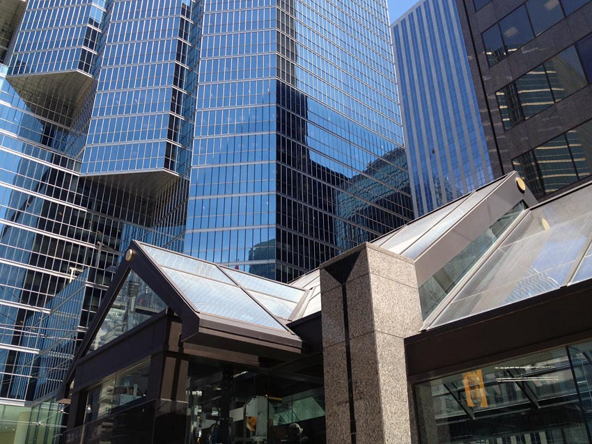 A-frame roofs in glass and granite columns with triangular incisions at top stand before soaring skyscrapers