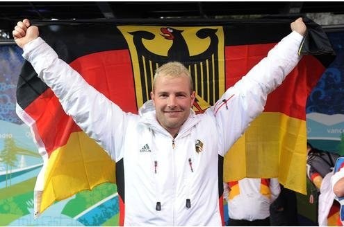 Bleach-blond Lange holding German flag behind him like a cape