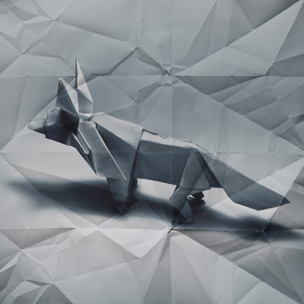 Fox made from folded grey paper on unfolded grey-paper background