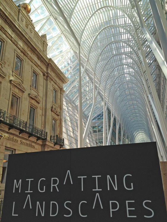 Migrating Landscapes poster (with crossbarless As) sits in the foreground of the vaulted Calatrava atrium and original façade at BCE Place