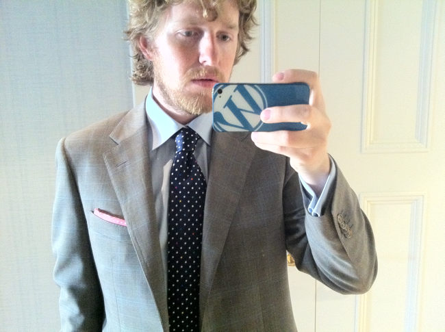 Straggly-bearded young man in suit (with pink pocket square) and WordPress-backed iPhone