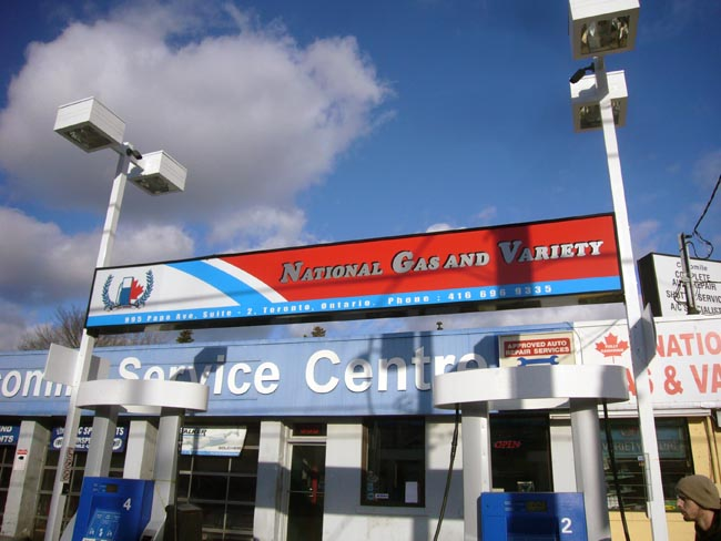 Gas station, in deep shadow, has sign reading NATIONAL GAS AND VARIETY in Cooper Black fake small caps