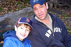 Chris Nutile in baseball cap and zip-up hoodie alongside nephew
