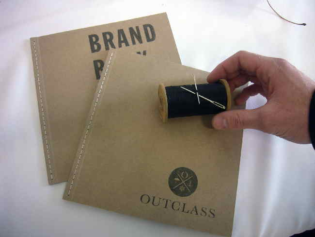 Tan-coloured Outclass brand books, plus needle and thread
