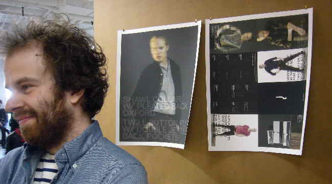 Bearded, scraggly-haired Markus before two printouts of his ad campaign
