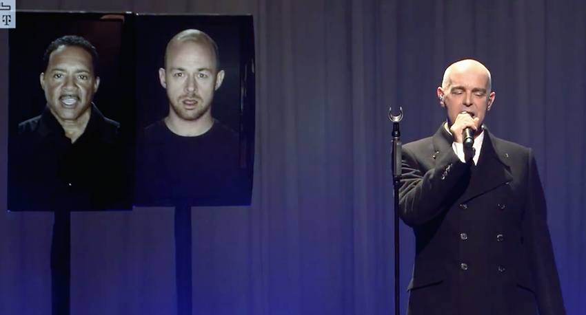 Neil Tennant singing alongside two vertical monitors showing male singers' faces