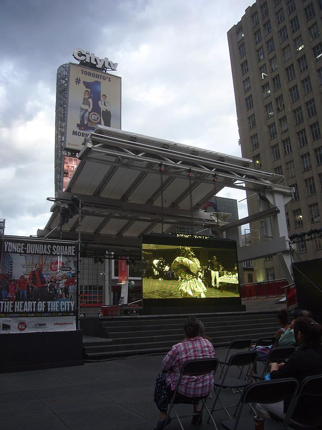 Man in giant lamé dress on video screen in open square