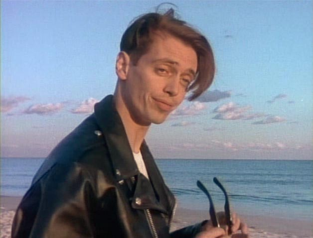 Steve Buscemi as Nick Spangler, standing on the beach, holding his shades, and looking our way