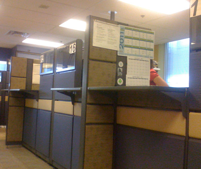 Cubicles with taped-on paper indicators in Arial