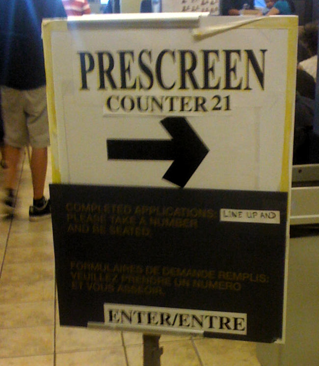 Standup sign with taped-on paper strips reading PRESCREEN COUNTER21