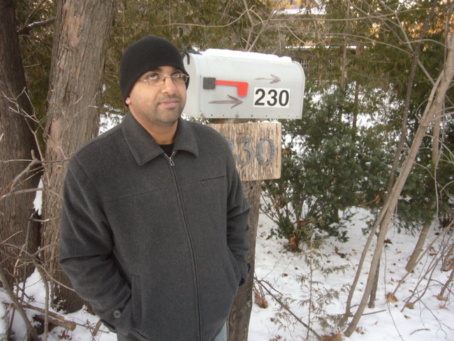 Man in toque outside rural-looking mailbox