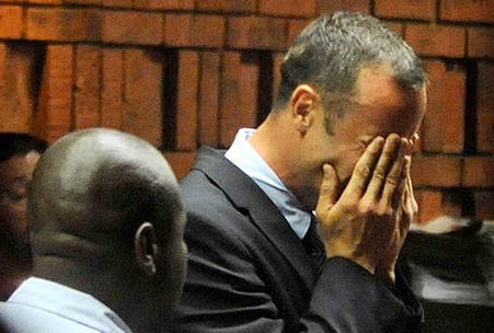 Pistorius stands in court, holding his face in his hands