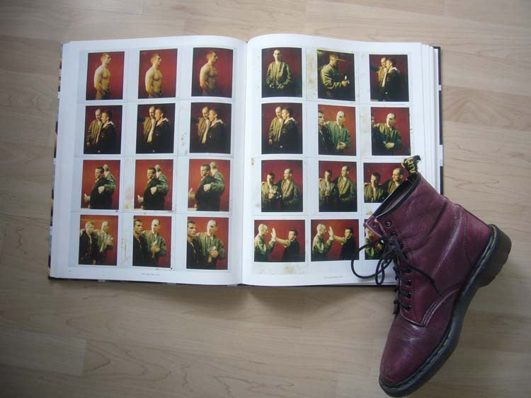 Cherry Doc Marten sits propped on corner of double-page spread of Polaroid photos of skinhead dudes
