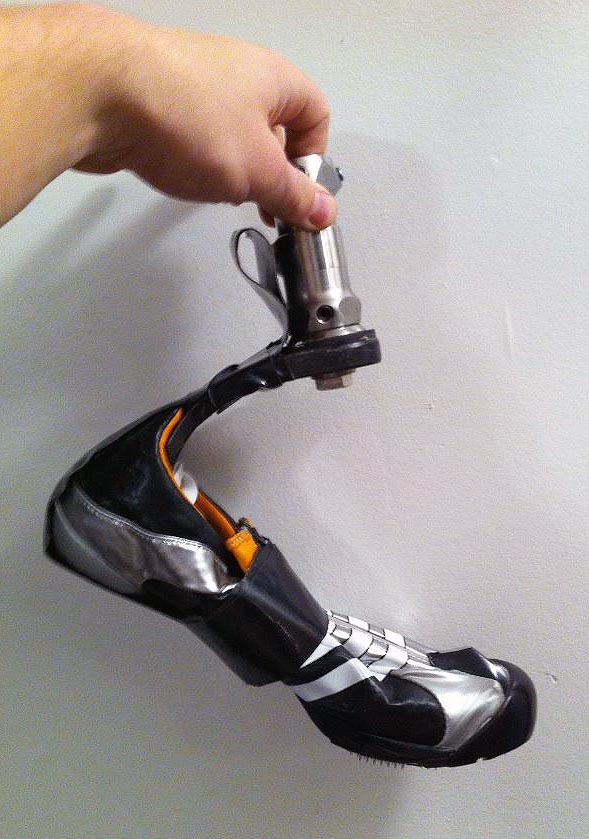 Hand holds angled prosthetic ankle and foot, which wears a crumpled bobspike shoe