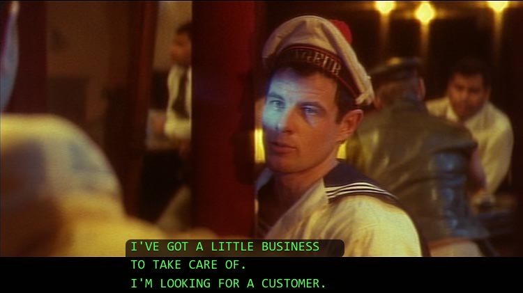 Brad Davis, in sailor cap, hugging a pole: I've got a little business to take care of. I'm looking for a customer