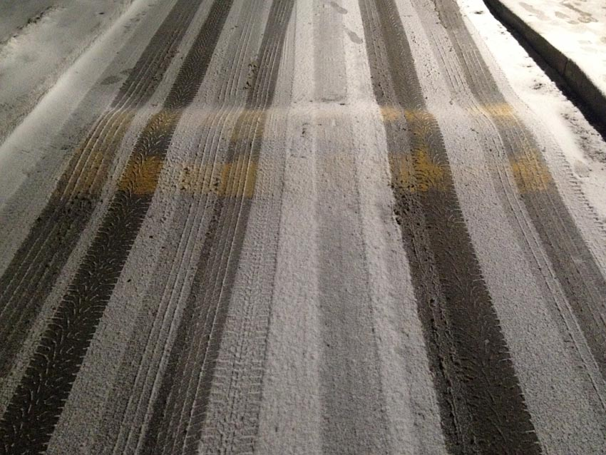 Parallel bands of tracks in the snow trace over a speed bump