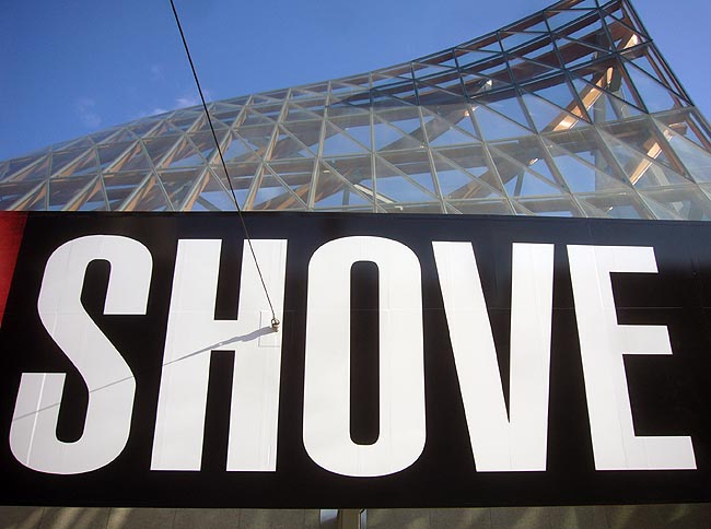 SHOVE on giant sign under soaring peaked glass roof