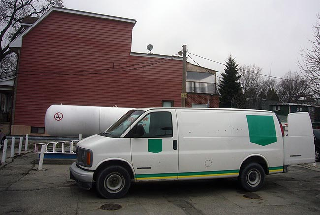 Plain van outside propane-refuelling station has shields painted on its sides, but nothing inside those shields